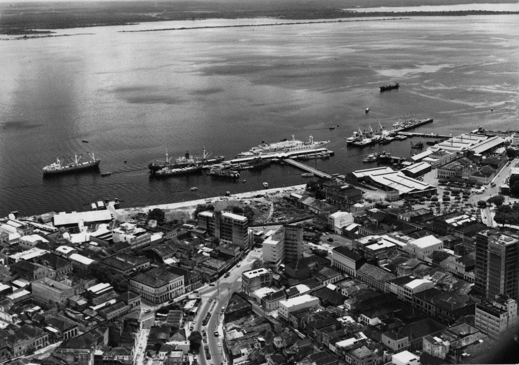 Vista aérea do Rio Negro e suas embarcações, ancoradas então. Além disso, estaque para a avenida Floriano Peixoto e rua dos Andradas.